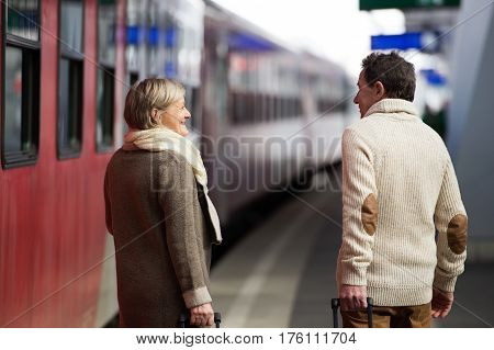 Beautiful senior couple on trainstation pulling a trolley luggage. Rear view.