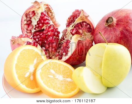 Ripe fruit: pomegranate orange apple sliced on a white background. A ring of orange an apple slice and a piece of pomegranate.