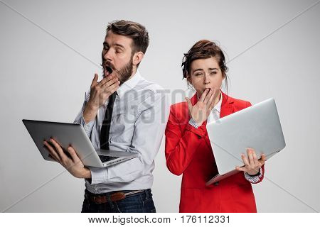 The  yawning and bored young businessman and businesswoman with laptops on gray background. The concept of relationship of colleagues.