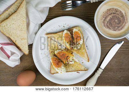 Boiled egg open sandwich on white bread seasoned with ground pepper with a cup of fresh cappuccino coffee sliced bread and utensils on a wooden table