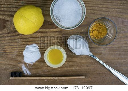 DIY toothpaste with ingredients lemon coconut oil turmeric baking soda Xylitol and bamboo toothbrush