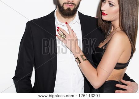 Sexy rich couple posing at white wall closeup