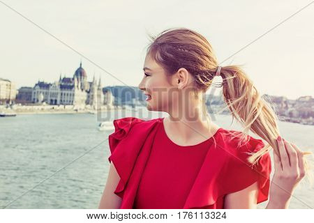 Happy young woman in red dress enjoying Budapest panorama Hungary