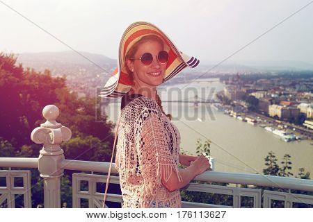 Young woman in hat enjoying Budapest panorama in retro style