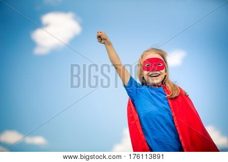 Funny little girl plays super hero over blue sky background. Superhero concept.