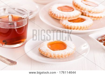 Teatime biscuits with tea on white dish.