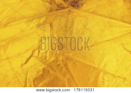 Gold thread on the fabric. Gold texture glitter background. Macro shot.