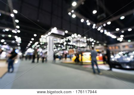 Blurred defocused background of public event exhibition hall showing cars and automobiles business commercial event concept