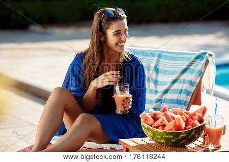 Beautiful brunette girl smiling, drinking cocktail, sitting  near swimming pool. Copy space.