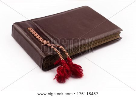 side view of vintage photo brown album cover with red lace bindings isolated on white background