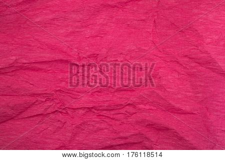 front view of crumpled paper background texture made from a dark pink sheet of wrapping paper