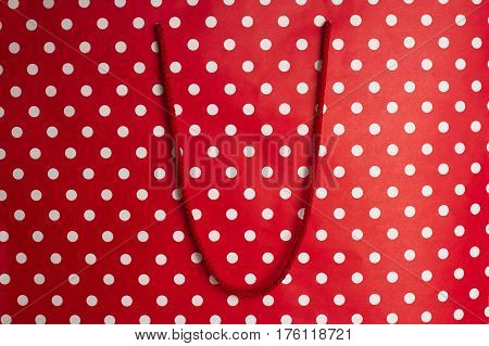 horizontal front view of red shopping bag background texture with polka dots and textile handle