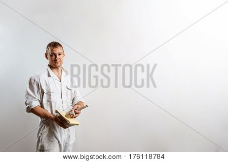 Professional worker looking at camera, holding sandpaper over white wall. Copy space.