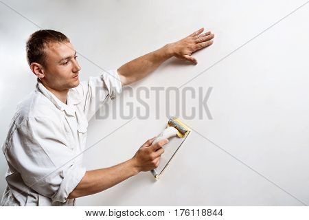 Professional worker grinding white wall with sandpaper. Copy space.
