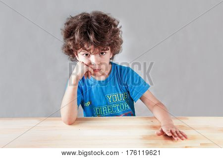 The amusing curly-headed kid angrily looks in the camera. On a gray background. Close up.