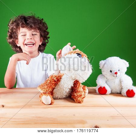 Happy laughing baby playing with his toys/ Favorite animals rejoice together with it. On a green background.