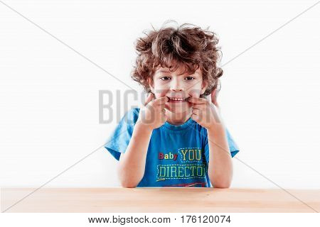 The ridiculous curly-headed kid having thrust fingers into a mouth wriggles in front of the camera. On a gray background. Close up.