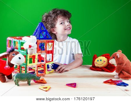 Happy joyful brown-eyed boy close up in white t-shirt is building a business center together with their toys. Toys help to build the house. On a green background.