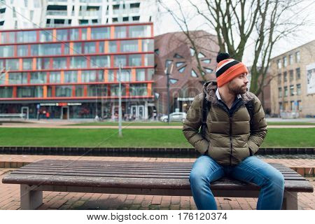 A young guy is sitting on a park bench.