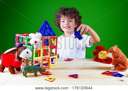Cute baby in white t-shirt is building a house and looking into the camera. Home construction. Toys help to build a house. On a green background.