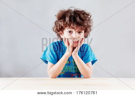 The lovely curly-headed kid in a blue t-shirt having inflated cheeks looks in the camera. On a gray background. Close up.