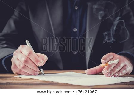 Smoking Businessman Signing Formal Letter. Stressful Atmosphere With Dark Background.