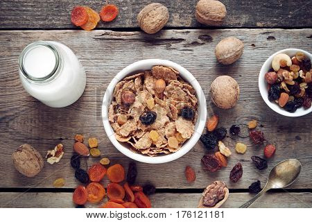 Ingredients for healthy breakfast: cereal wheat flakes in bowl dried fruits muesli and milk bottle on wooden table. Top view flat lay.
