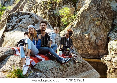 Young friends sitting on rock in canyon, smiling, drinking tea. Copy space.