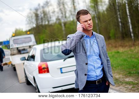 Man calling while tow truck picking up his broken car.