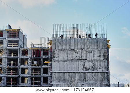 workers knit rebar standing on the edge of the house