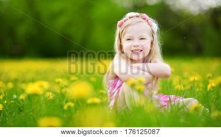 Adorable Little Girl In Blooming Dandelion Meadow On Beautiful Spring Day