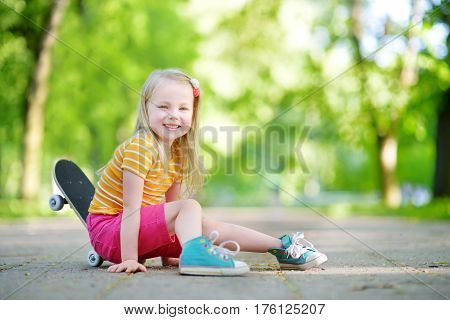Pretty Little Girl Learning To Skateboard On Beautiful Summer Day In A Park