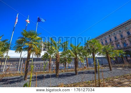 Famous palms trees in Milan Dome square. The Duomo Cathedral in a blue sky day. Tourists in Piazza Duomo square. Waving flags of Italy, Milano and Europe.