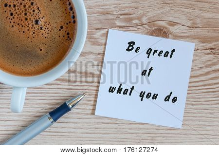 Be great at what you do - motivational concept at notepad with morning mug of coffee.