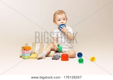 Adorable baby boy sitting on the floor and playing with some toys.