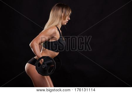 Beautiful fitness woman is lifting a barbell. Sporty girl showing her well trained body. isolated on dark background with copyspace.
