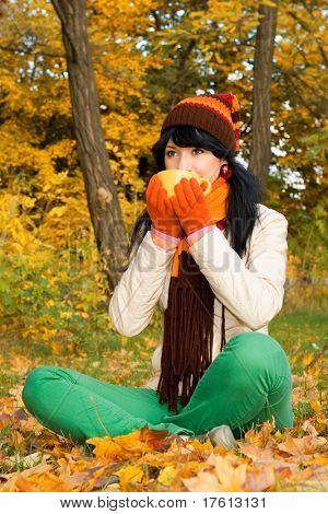 Young pretty woman with tea cup in the autumn park