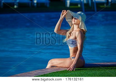 Beautiful young woman is sitting on ledge of swimming pool and looking away