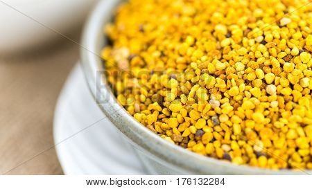 close up shot grains of bees pollen in a ceramic dish with brown cloth background shot in narrow depth of field copy space to the left