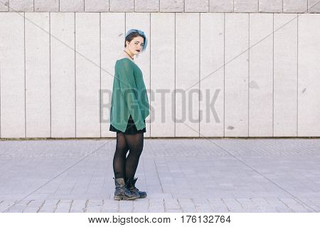 full body of a teen androgynous woman with blue dyed hair isolated on the street wearing a blue sweater.