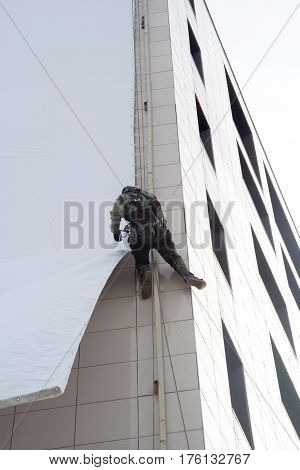 An industrial climber hangs an advertising banner on a commercial building extreme