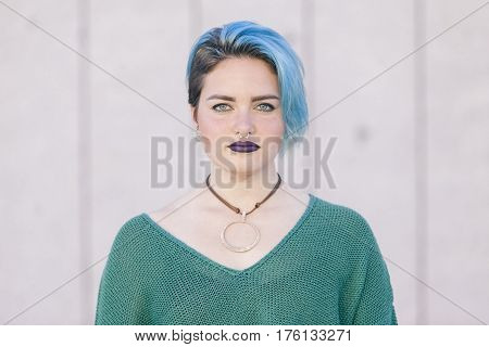Teen androgynous woman with sad expression and blue dyed hair isolated on the street wearing a nose piercing