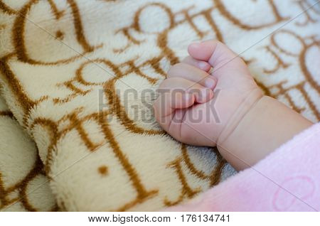Close up of hand asian baby on the bed.
