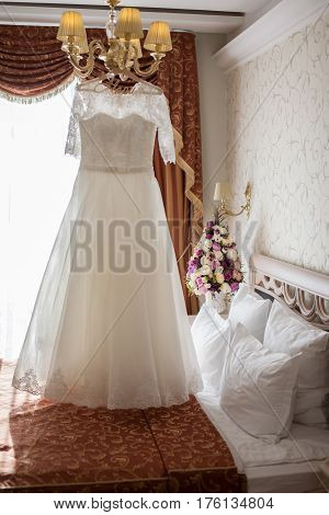 Wedding dress hanging on a chandelier above the bed