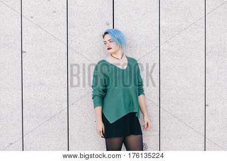 Teen androgynous woman with blue dyed hair isolated on the street wearing a blue sweater.