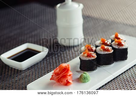 Traditional Japanese sushi on a white plate with sauce