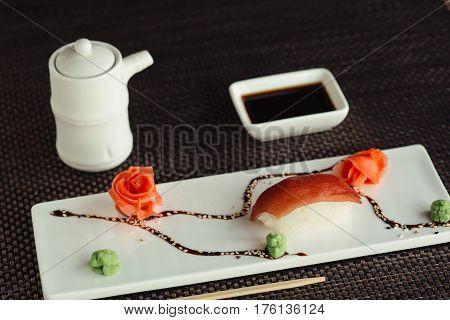 Japanese tuna sushi on white dish with sauce, presentation