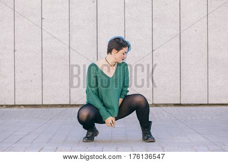 full body of a young androgynous woman with blue dyed hair isolated on the street wearing a blue sweater.
