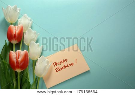 Beautiful white and red tulips with envelope on a light turquoise background. Happy Birthday card