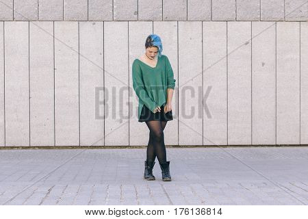 teen androgynous woman looking down with blue dyed hair isolated on the street wearing a blue sweater.